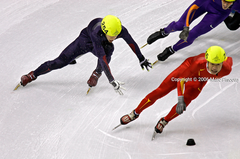 U.S. Short Track skater and former gold medalist Anton Apolo Ohno (#254) tries to stay upright after losing his balance in a corner near Chinese skater LI ye(#216) at the Men's 1500 Meter Short Track Speed Skating event at the Palavela ice arena in Turin, Italy on February 12, 2006. Defending gold medalist Anton Apolo Ohno did not qualify for the finals after losing his balance in one of the final turns of the race..(Photo by Marc Piscotty / ©2006)