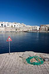 Cartello di pericolo caduta in acqua alla fine del molo nel porto di Gallipoli (LE). Dietro alcuni edifici della città vecchia tra cui anche l'ex mercato coperto, da poco restaurato.