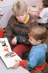 Nursery school teacher reading story book with pupil,