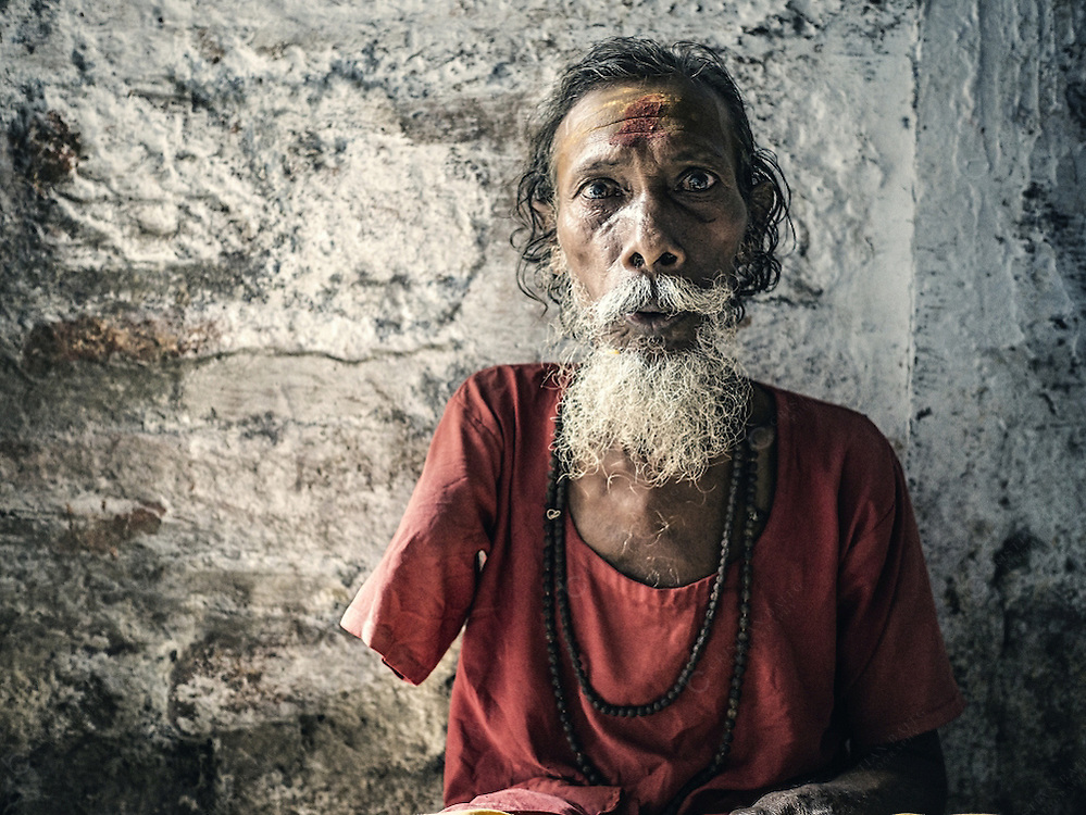 Varanasi, India - October 06, 2015Handicapped beggar in ascetic clothes asking for money in an alley in Varanasi India. With the high affluence of pilgrims and tourism many destitute and poor people beg in the streets many in ascetic clothes so to have a higher chance to receive attention from people.