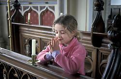 Small girl praying in church UK