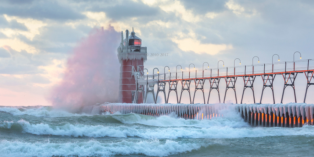The setting sun lending some color to the waves crashing against the lighthouse in South Haven.
