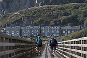 Male walkers cross Barmouths pedestrian and rail bridge on the Mawddach Estuary, on 13th September 2018, in Barmouth, Gwynedd, Wales.