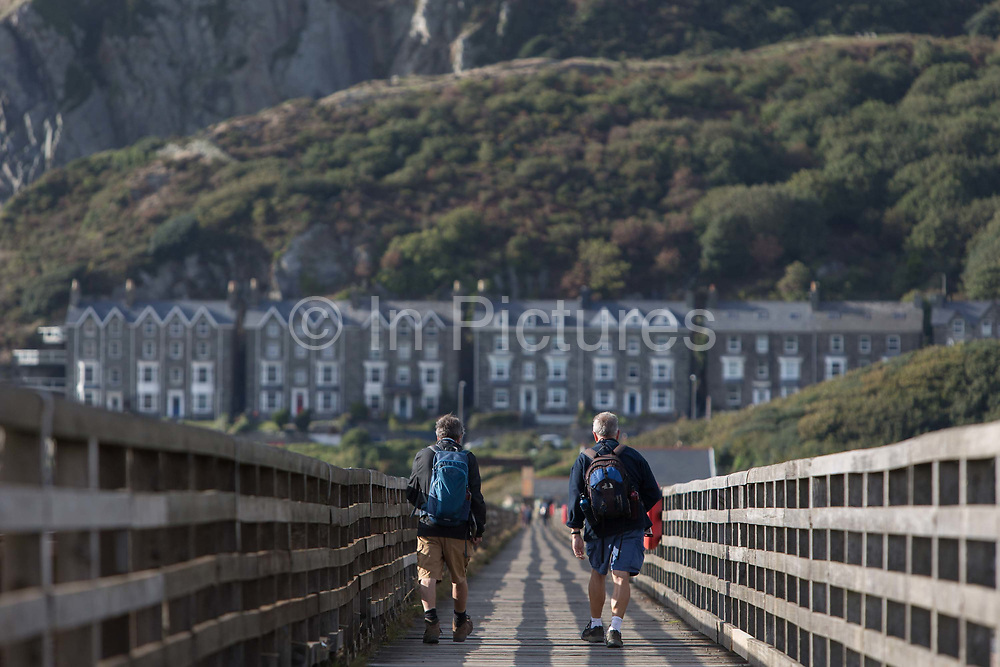 Male walkers cross Barmouths pedestrian and rail bridge on the Mawddach Estuary, on 13th September 2018, in Barmouth, Gwynedd, Wales.