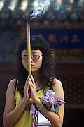 A young woman prays as she burns incense at Tanzhesi Temple in western Beijing. Situated in the Western Hills, this Buddhist temple lies 45km west of Beijing. The temple name means 'Dragon Pool and Mulberry Tree Temple', due to its proximity to the Dragon Pool and the trees growing in the surrounding hills.....