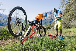 Mountainbikers repairing flat type on E-bike