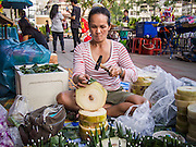 "17 NOVEMBER 2013 - BANGKOK, THAILAND:  A woman makes krathongs to sell to temple goers near Wat Yannawa on Loy Krathong. Loy Krathong (also written as Loi Krathong) is celebrated annually throughout Thailand and certain parts of Laos and Burma (in Shan State). The name could be translated ""Floating Crown"" or ""Floating Decoration"" and comes from the tradition of making buoyant decorations which are then floated on a river. Loi Krathong takes place on the evening of the full moon of the 12th month in the traditional and they do this all evening on the 12th month Thai lunar calendar. In the western calendar this usually falls in November. The candle venerates the Buddha with light, while the krathong's floating symbolizes letting go of all one's hatred, anger, and defilements      PHOTO BY JACK KURTZ"