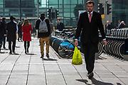 A male city worker walks across the plaza near the Barclays bike park outside Canary Wharf tube station in Docklands, London, United Kingdom.