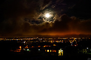 A full moon rises over Imbabura volcano in Cotacachi, in a very cloudy night sky.. The town's lights are shinning brightly.