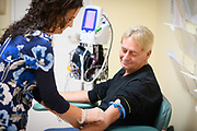 Photography inside the Volunteers in Medicine in Stuart, a Florida Healthcare Clinic of a medical assistant taking the blood pressure of a patient.