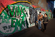Two people walk passing grafitti along the towpath of Regents Canal. This area is known as a good site fro street art, although sometimes the grafitti is of a pretty low standard.