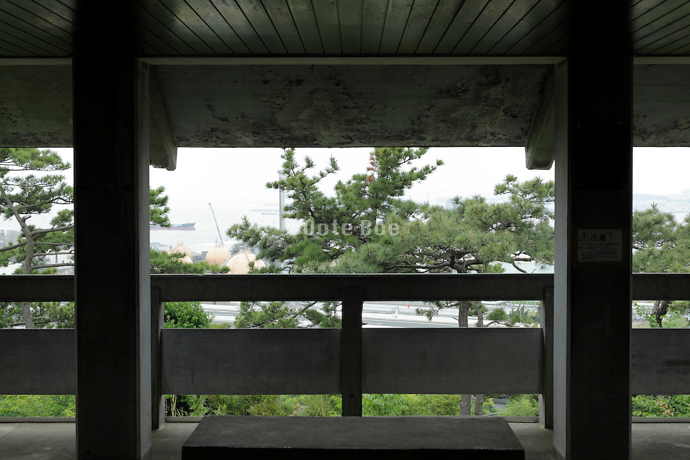 concrete building lookout at edge of nature garden with highway seen behind the trees Japan Yokohama