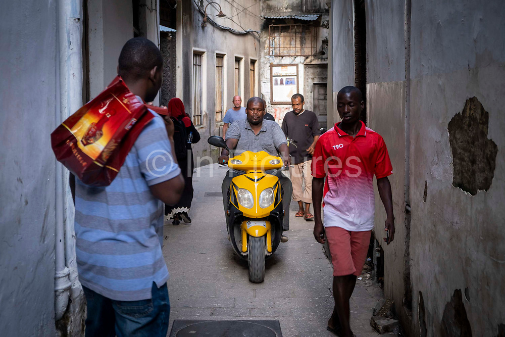 Mopeds and pedestrians share the small streets of the tourist area Shangani, in the heart of Stone Town, Zanzibar, Tanzania.