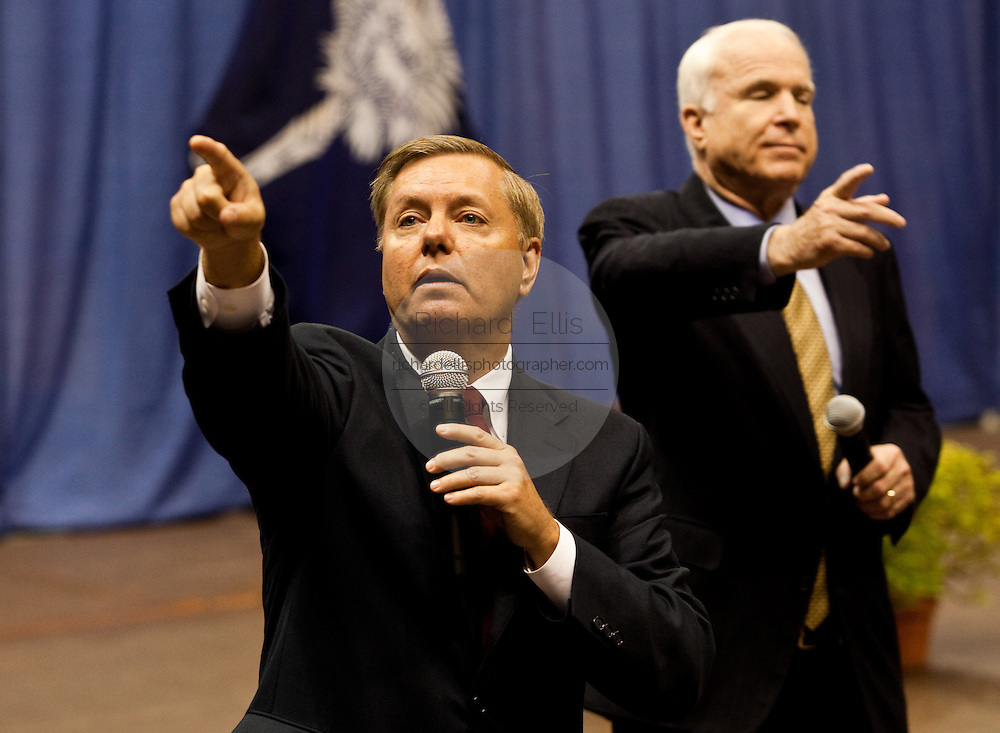Sen. Lindsay Graham (L) calls on a citizen as Sen. John McCain (R) does the same during a health care town hall meeting September 14, 2009 at the Citadel in Charleston, SC.