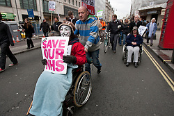 © licensed to London News Pictures. London, UK 17/03/2012. A disabled UK Uncut protester with a anonymous mask marching in Strand as the protesters started to march after the protest outside Department of Health, London, against the Government's Health and Social Care Bill currently passing through Parliament. Photo credit: Tolga Akmen/LNP