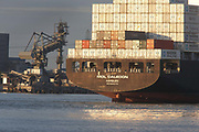 The Hamburg-registered Mol Caledon ship passes the giant dredging machinery at npower's Tilbury power station on the  River Thames northern shore, Essex England. Having just departed from Tilbury Docks with the evening sun glinting off the stern's reflective surfaces, stacks of tall containers are heaped high but evenly spread for stability along the massive vessel. They head out towards open sea, navigating through deeper water channels that naturally get shallower as silt chokes the waterways. Historically, the Thames has long been a route for shipping that kept the capital supplied and although the docks have seen huge decreases in traffic and volume since the second world war, Tilbury remains a busy hub for containerized vessels arrivng from all over the world.