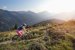Two mountain bikers riding on hill in alpine landscape, Zillertal, Tyrol, Austria