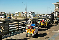 NC01401-00...NORTH CAROLINA - Carts beloning to the fishermen on the busy deck of Jennettes Pier and a surf competition on the Outer Banks at Nags Head.