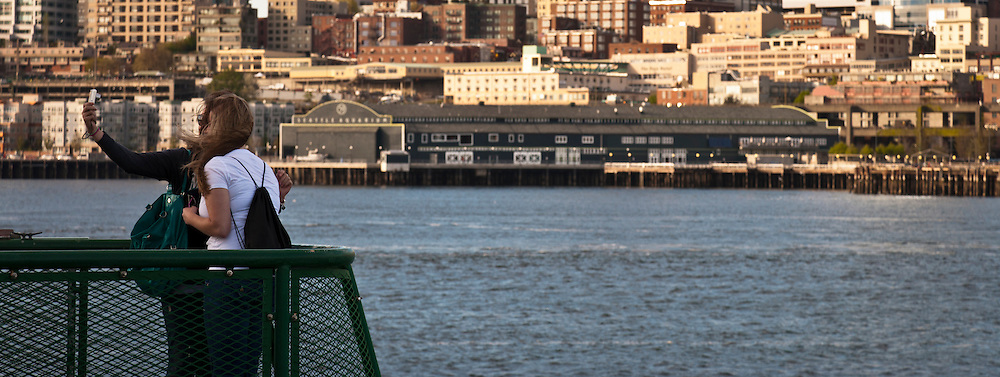 two people pose to make a self portrait on a ferry in Puget Sound - arriving in Seattle, WA, USA