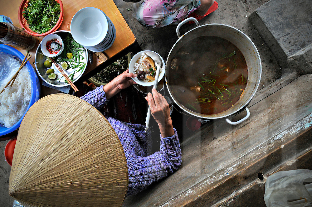 Top view of a Vietnamese woman ladling noodle soup into a bowl from a large pot, Hue, Vietnam, Southeast Asia