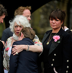 © Licensed to London News Pictures. 18/04/2016. Shirley, UK.  Ronnie Corbett's wife, Anne (left) comforts a young boy while stood next to her fighter Sophie (left) following the funeral of comedian, actor, writer Ronnie Corbett at St John the Evangelist Church in Shirley near Croydon. Corbett, who was most famous for his comedy sketch show  The Two Ronnies, performed with the late Ronnie Barker, died at the age of 85. Photo credit: Ben Cawthra/LNP
