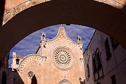 Uno scorcio della cattedrale di Ostuni inquadrata da dietro l'arco della curia vescovile.