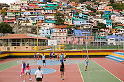 Girls and two men play volleyball in the 12 de Octubre barrio in Caracas, Venezuela.