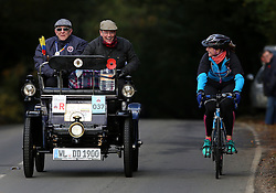Participants in the Bonhams London to Brighton Veteran Car Run are overtaken by a cyclist as they head up Holmsted Hill near Crawley, Sussex.