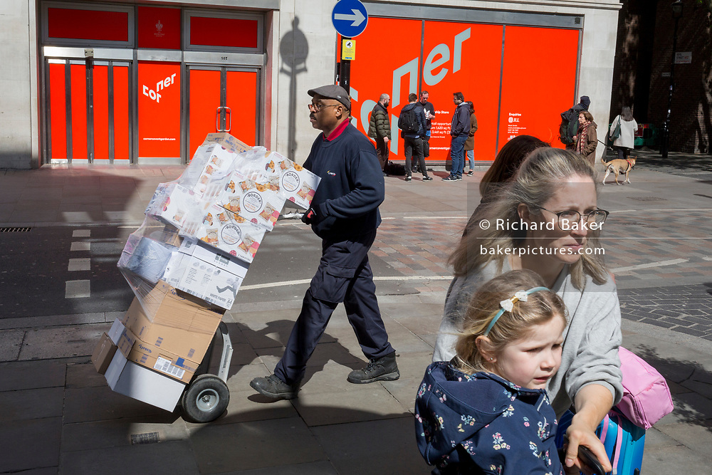 A delivery man pushes a trolley of boxes past a lady and child on Long Acre near Covent Garden, on 9th May 2019, in London, England.