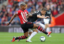 """Southampton's Mario Lemina (left) and Burnley's Johann Gudmundsson battle for the ball during the Premier League match at St Mary's, Southampton. PRESS ASSOCIATION Photo. Picture date: Sunday August 12, 2018. See PA story SOCCER Southampton. Photo credit should read: Andrew Matthews/PA Wire. RESTRICTIONS: EDITORIAL USE ONLY No use with unauthorised audio, video, data, fixture lists, club/league logos or """"live"""" services. Online in-match use limited to 120 images, no video emulation. No use in betting, games or single club/league/player publications."""