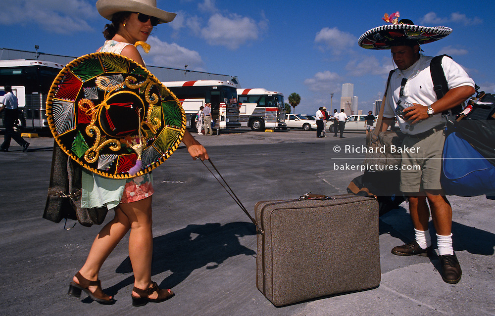 Having just disembarked from a Carnival Cruise ship at the port of Miami, Florida, two tourists carry and pull their baggage along to a waiting coaches that will transport them for onward journeys. Comically they also wear wide sombrero hats bought in Cancun during their vacation around the Gulf of Mexico, the destination of this popular cruise line whose base is Miami. Stitched with garish colours the souvenirs provide shelter from the overhead tropical sun though the woman of this couple chooses to hang hers over a shoulder and keeps her original hat on her head. This may be the couples' honeymoon or just a special annual holiday away from the kids or a humdrum lifestyle where the weather is far from the intensity of Florida, a favourite resort for Americans not liking foreign travel.