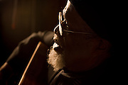 A close up shot of an african-american blues musician singing and playing his guitar in a low lit bar.