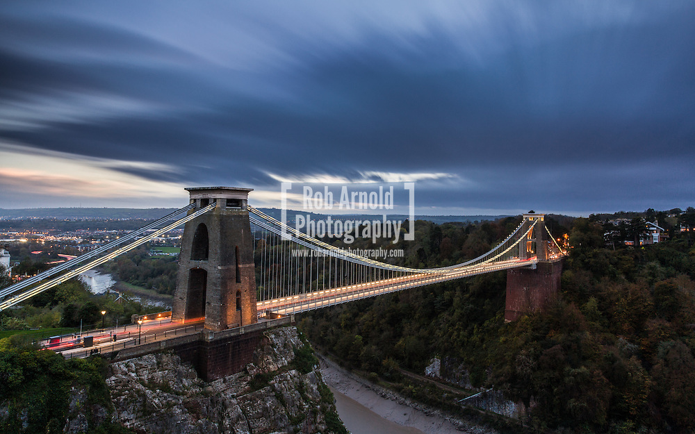 Brunel's Clifton Suspension Bridge lit up at dusk on a cloudy and windy Autumn day.
