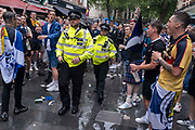 Scotland football supporters boo police officers while gathering in the rain near Londons Leicester Square before tonights match between England and Scotland at Wembley, during the European Championships postponed for a year because of the Covid pandemic, on 18th June 2021, in London, England. The two nations have traditionally been fierce sporting rivals and this is the first time that Scotland has qualified for the Euros for 23 years.