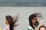 WENLING, CHINA - AUGUST 07: (CHINA OUT) <br /> <br /> Tourists holding umbrellas walk in strong wind and heavy rain near West Lake as Typhoon Soudelor approaches on August 7, 2015 in Hangzhou, Zhejiang Province of China. Typhoon Soudelor will land on southeastern China\'s coastal areas early Saturday, according to meteorological departments<br /> ©Exclusivepix Media