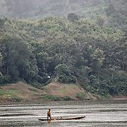 A man paddles his wooden fishing canoe on the Nam Ou (River Ou) in Nong Khiaw in northern Laos. In the background, mists shroud the rugged terrain. About 2/3 of the way up the frame are some thing white lines that are power lines crossing the river.