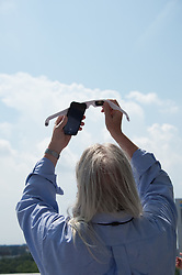 A NASA employee use protective glasses over his  cell phone to capture and view a partial solar eclipse from NASA Headquarters Monday, Aug. 21, 2017 in Washington, DC. A total solar eclipse swept across a narrow portion of the contiguous United States from Lincoln Beach, Oregon to Charleston, South Carolina. A partial solar eclipse was visible across the entire North American continent along with parts of South America, Africa, and Europe.  Photo Credit: (NASA/Connie Moore)