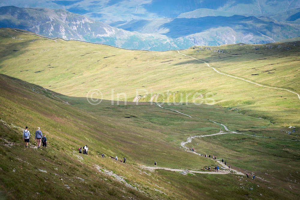 Walkers make their down the paths after climbing Helvellyn Mountain in The Lake District, Cumbria, United Kingdom on the 2nd of August 2021. Helvellyn is the third-highest point in England and is located in the beautiful Lake District National Park and part of the Eastern Fells.