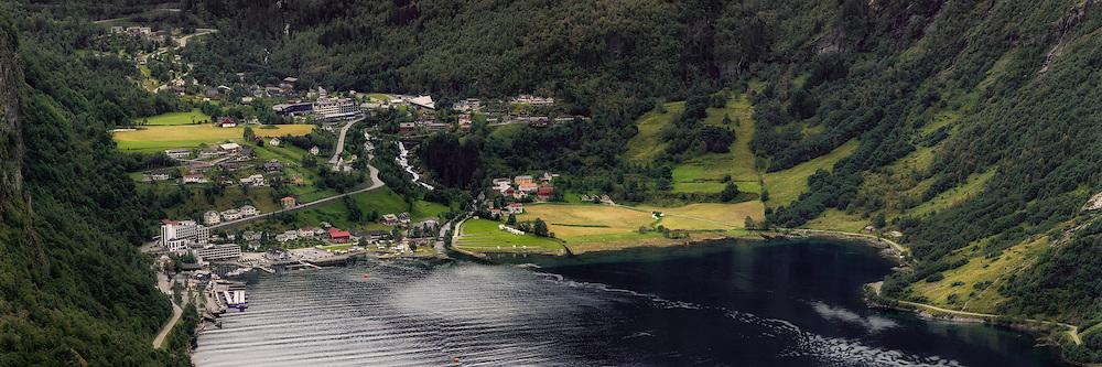 The village Geiranger is located at the end of Geirangerfjord, and is located in the Norwegian county Møre og Romsdal. Geirangerfjord is a 15 km long arm of Storfjorden. The panorama picture is captured from the viewpoint Ørnesvingen, and is stitched together by 5 single frames   Tettstedet Geiranger, i enden av Geirangerfjord ligger på Sunnmøre i Møre og Romsdal. Den 15 kilometer lange fjorden utgjør en arm av Storfjorden. Bildet, et panorama sett sammen av 5 enkeltbilder, er tatt fra utsiktspunktet i Ørnesvingen.