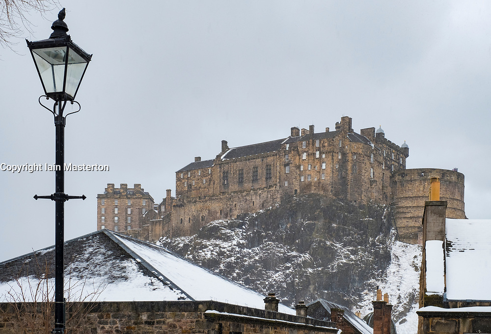 View of Edinburgh Castle across snow covered roofs of houses , Scotland, United Kingdom