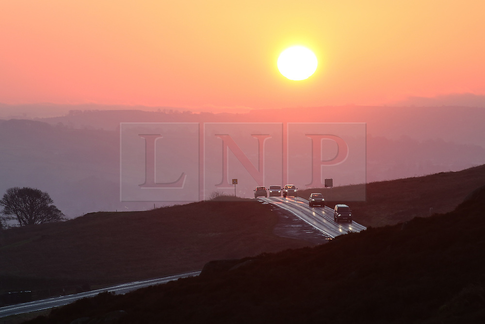 © Licensed to London News Pictures. 25/01/2017. Ilkley, UK. Commuters make their way over Ilkley Moor as the sun rises on a cold January morning in West Yorkshire. Temperatures were milder this morning but most of the country still saw thick fog. Photo credit : Ian Hinchliffe/LNP