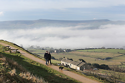 © Licensed to London News Pictures. 06/02/2017. Huddersfield, UK. A couple walk their dog on Castle Hill in the sunshine as thick banks of fog cover Huddersfield on a cold February morning in West Yorkshire. Forecaster are predicting heavy rain this week but none was in sight here as the sun began to shine and burn through the dense fog. Photo credit : Ian Hinchliffe/LNP