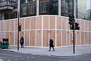 Woman wearing a face mask in front of a wooden hoarding surrouding a building on Oxford Street which is empty of shoppers as the national coronavirus lockdown three continues on 28th January 2021 in London, United Kingdom. Following the surge in cases over the Winter including a new UK variant of Covid-19, this nationwide lockdown advises all citizens to follow the message to stay at home, protect the NHS and save lives.