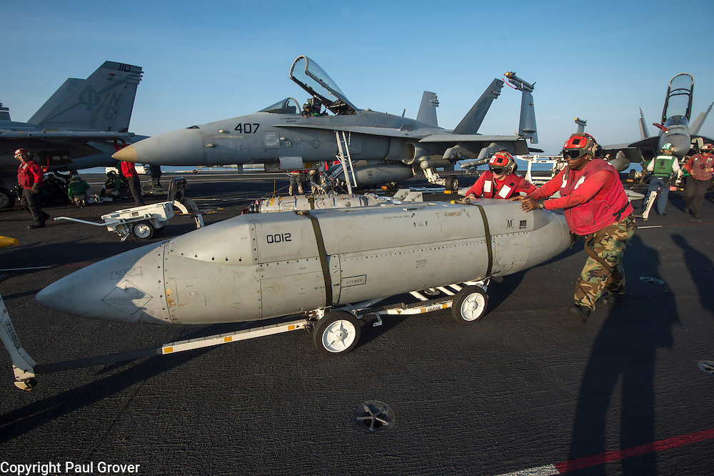 USS John C Stennis CVN-74 Aircraft Carrier.Pic Shows Flight and Hangar Deck wearing red shirts personnel  loading  ammunition and weapons