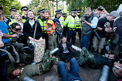 © London News Pictures. 19/08/2013. Balcombe, UK. Activists attach themselves together in front of police at the entrance to the Cuadrilla drilling site in Balcombe, West Sussex on a day of of civil disobedience organised by campaign group No Dash For Gas. Cuadrilla has temporarily ceased drilling at the site, which has been earmarked for fracking, under advice from the police. Photo credit: Ben Cawthra/LNP