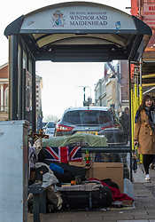 """A homeless man sleeps under a bundle of blankets in the bus shelter on Windsor High Street that has been his home for months. After a public outcry against their """"homelessness support strategy"""" where rough sleepers would have been fined £100, Windsor council has shelved their plans. Windsor, Berkshire, February 16 2018."""