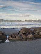 Looking over the famous Moeraki Boulders (Kaihinaki), towards the town of Moeraki, Moeraki Beach,  New Zealand.