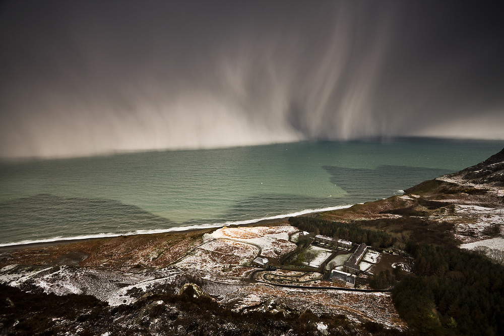 Nominated in 10th (2017) International Colour Awards (Nature category) <br /> <br /> A huge snow blizzard sweeps over a green Irish Sea towards the tiny hamlet of Nant Gwrtheyrn, once the centre of a busy granite quarrying community on the North coast of the Llyn Peninsula, Wales. This is now a post industrial landscape of abandoned granite quarrying buildings and levels. The hamlet is now a Welsh language and conference centre.<br /> <br /> From my book Nant Gwrtheyrn - Y Swyngyfaredd (The Enchantment)<br /> <br /> This book is available for purchase here on www.glyndavies.com