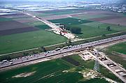 Nederland, Zuid - Holland, Zoetermeer, 17/05/2002; kruising van de HSL (in aanleg) met autosnelweg A 20 (en filevorming!); kassen gebied Bleiswijk aan de horizon; de HSL zal de bestaande infrastructuur (inclusief  spoorlijn Den Haag - Gouda)  op kolommen kruisen; verkeer en vervoer, infrastructuur, bouwen, spoor, rail, TGV planologie ruimtelijke ordening, landschap tuinbouw;<br /> luchtfoto (toeslag), aerial photo (additional fee)<br /> foto /photo Siebe Swart