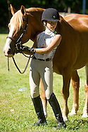 Middletown, New York - A young girl stands by her horse as she waits to ride in the 70th annual Middletown Rotary Horse Show at Fancher-Davidge Park on Sept. 8, 2013.